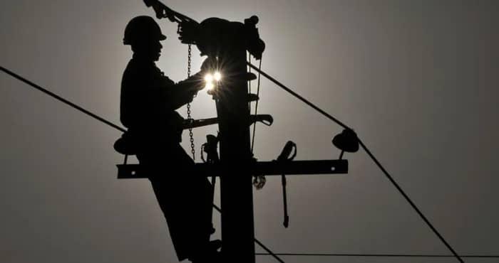 un homme travaillant sur un poteau electrique